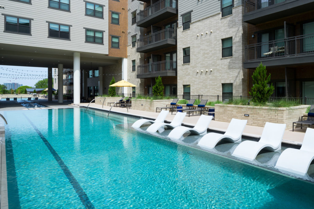 Resort-style pool and lounging area at Alexan Lower Greenville