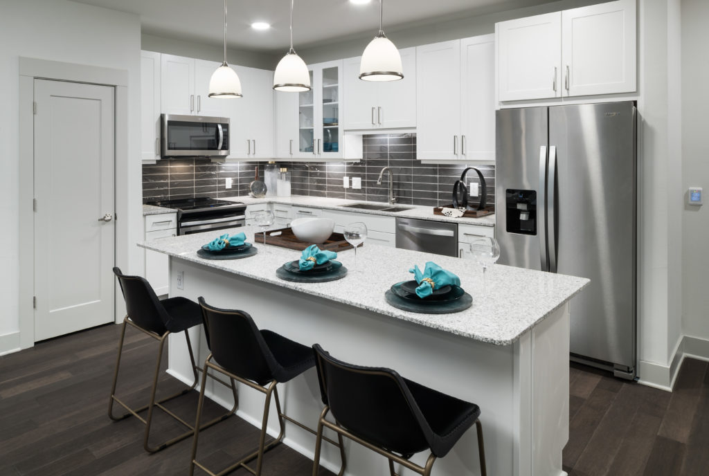 Stylish kitchen with granite countertops and stainless-steel appliances at Alexan Lower Greenville - Make a Move Toward Luxury